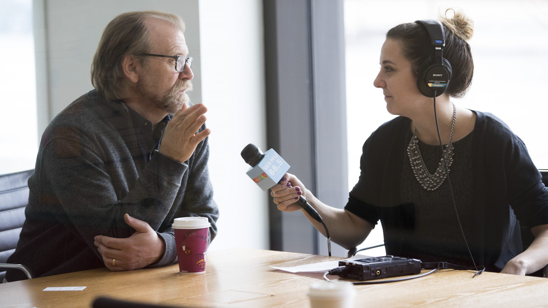 Mikaela Lefrak with headphones on holding a WAMU microphone interviewing a man seated at a table